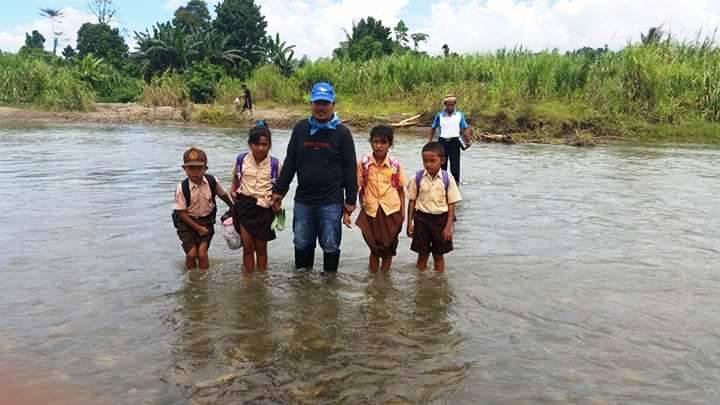 Uksin saat Menyeberang Sungai Bersama Anak Sekolah